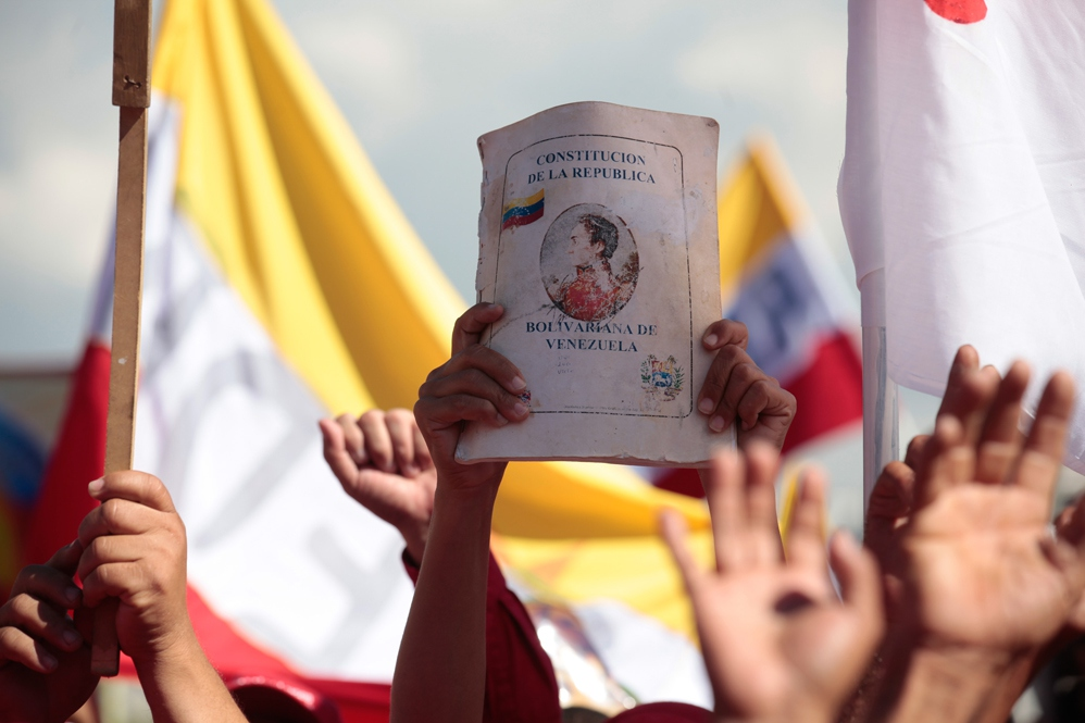 An activist holds up a copy of the Bolivarian constitution at a pro-government march held recently in Caracas, Venezuela (archive)