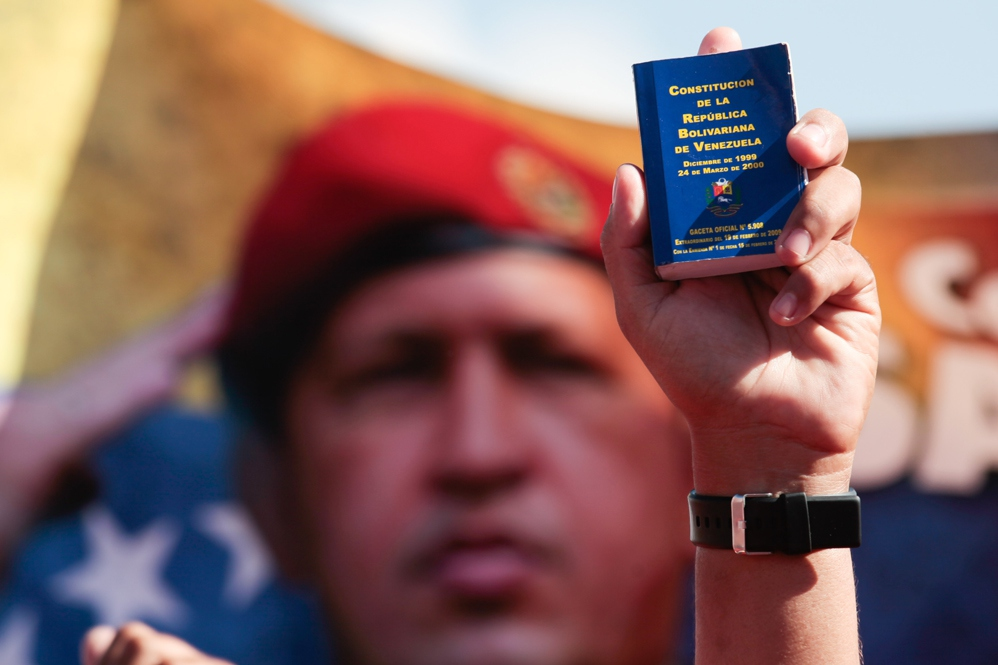 A Venezuelan holds up a copy of the 1999 constitution at a celebratory march in Caracas on Monday, with late president Hugo Chavez looming large on banners and signs. (Prensa Miraflores)