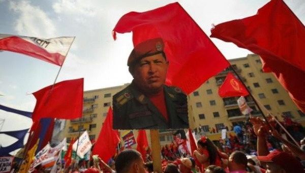 A supporter of Venezuela's President Nicolas Maduro holds up a picture of late president Hugo Chavez (PHOTO: Reuters)