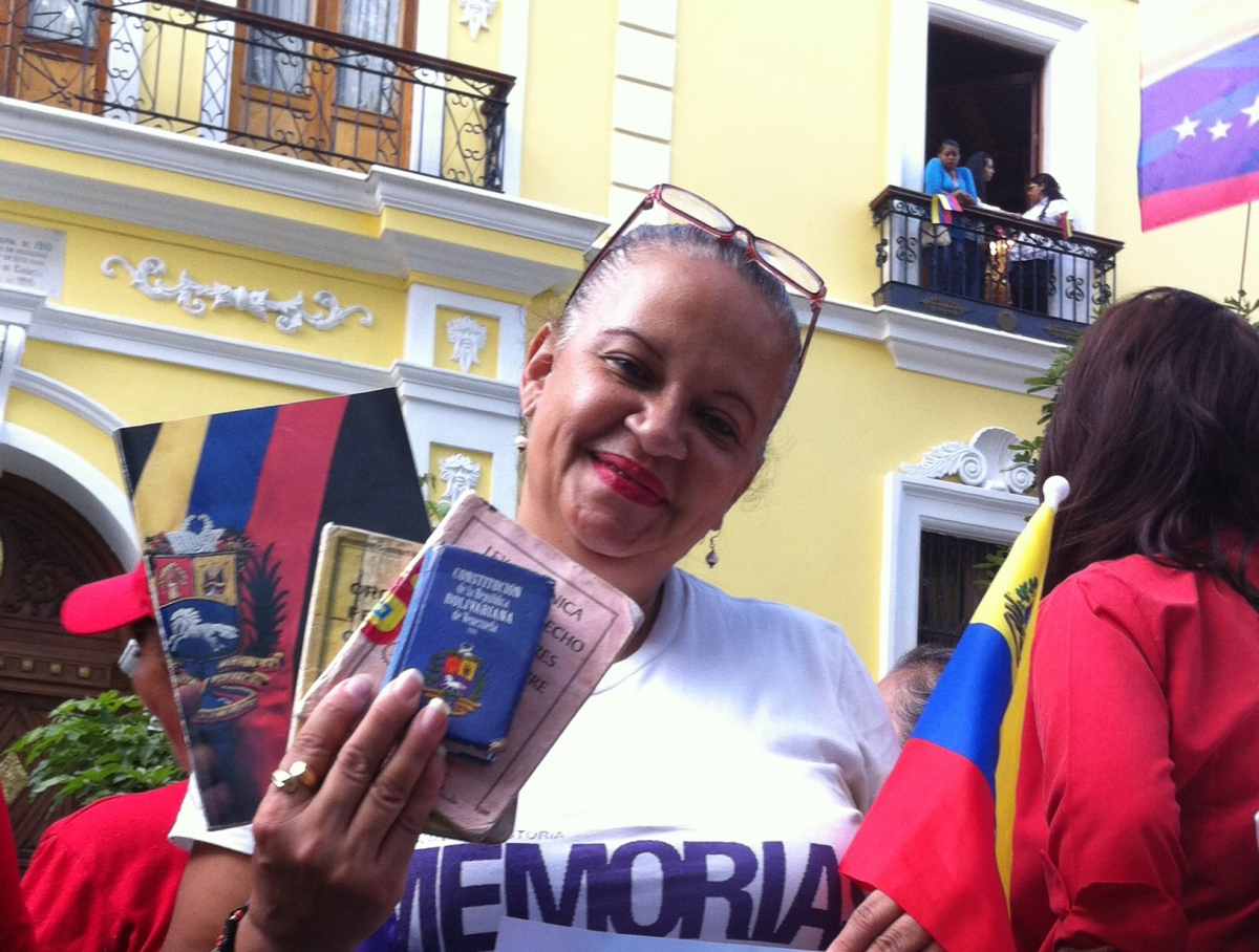 A woman shows her constitution and support for President Maduro at Plaza Bolivar on January 21. (Cory Fischer-Hoffman)