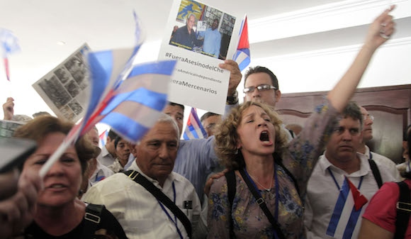 """A woman holds a banner from the protest in Panama - """"#GetOutChe'sAssassin, #OurIndependentAmerica #GetOutMercenaries"""" (Ismael Francisco/ Cubadebate)"""