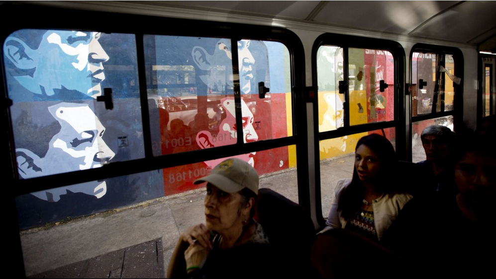 People ride on a public bus past a street mural of Venezuela's late President Hugo Chávez in Caracas.  (Photo: Ariana Cubillos/AP)