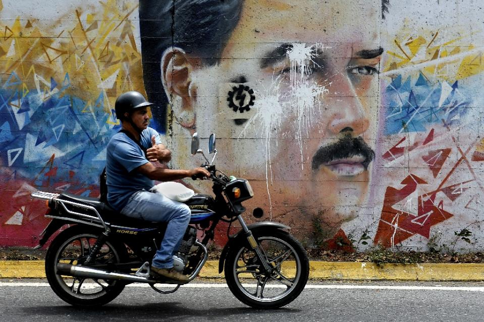 A motorcyclist passes by a graffiti depicting Venezuelan President Nicolas Maduro in Caracas on April 17, 2015 (AFP Photo/Federico Parra)