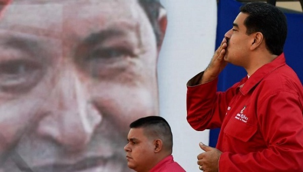 Venezuelan President Nicolas Maduro (R) blows a kiss during a rally with PDVSA workers outside the Miraflores presidential palace in Caracas on January 12, 2016. (AFP)