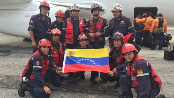 A Venezuelan rescue team poses for a photo as they prepare to board a plane to Ecuador to join rescue efforts after a massive earthquake, Sunday April 17, 2016. (teleSUR)