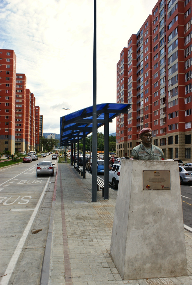 "A statute of Hugo Chávez commemorates the moment the government turned in the Housing Mission's very first apartment. In the background, a bus stop is visible. ""The Chinese area is the best part of Tiuna City. The most beautiful and the most well-arranged. The other areas are not as beautiful,"" says Ángel, who received his apartment two months ago. (Jonas Holldack/Venezuelanalysis)"