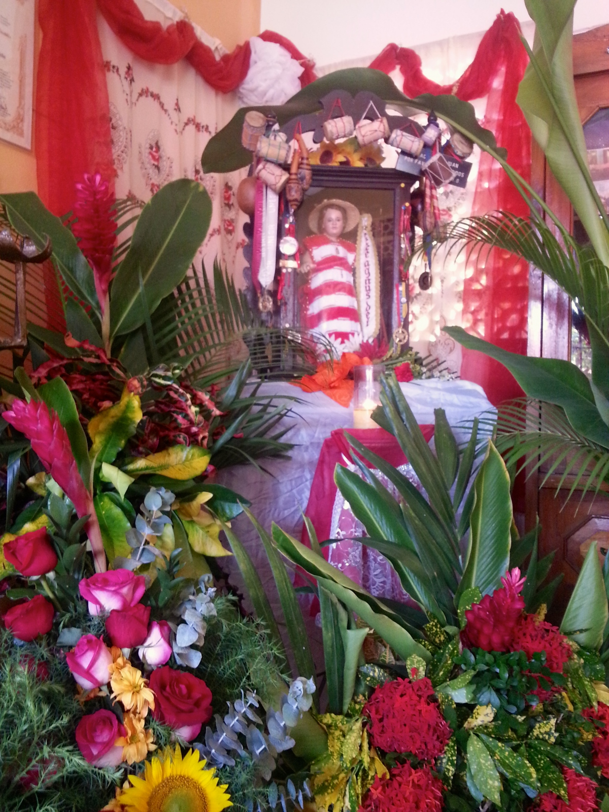 Devotees to San Juan arrive to the San Juan House and pay homage to the saint adorning his figure with flowers, instruments and letters outlining their wishes (Jeanette Charles/Venezuela Analysis).
