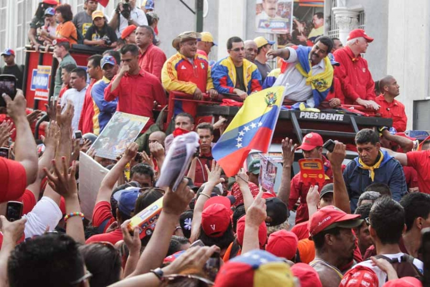 Nicolás Maduro (upper right, with flag tied around his neck) celebrates with the Venezuelan people in the streets of Caracas after his election as president in 2013 (Joka Madruga/Flickr).
