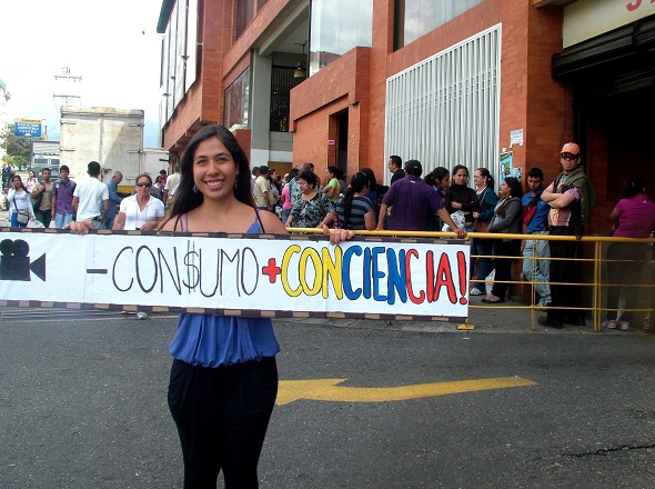 'Less consumerism, more consciousness' reads the placard of a young protestor outside a supermarket queue. (Tamara Pearson)