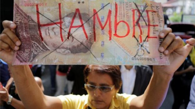 "Woman holds a large image of the 100 Bolivar currency note with the word ""hunger"" (Reuters)."