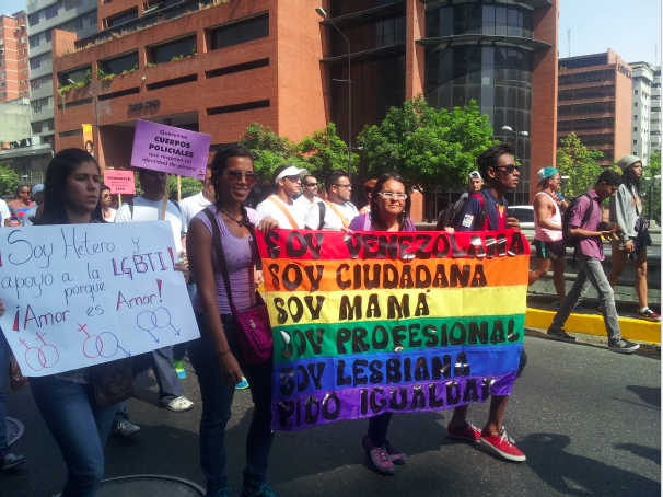 "Venezuelans participate in annual pride march. The rainbow colored posted reads: ""I am Venezuelan, I am a citizen, I am a mom, I am a professional and I am a lesbian. I ask for equality."" (Runrunes/@Boonbar)"