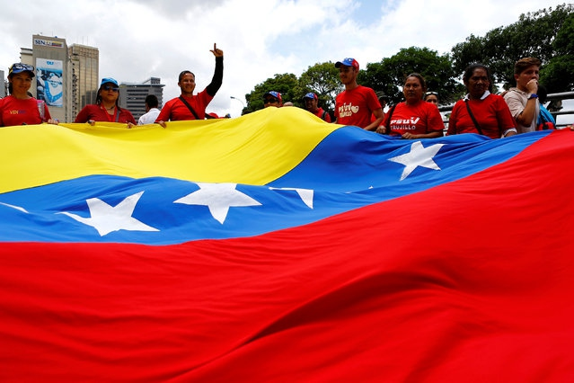 Supporters of the Maduro administration carry a Venezuelan flag during a march in Caracas, Venezuela on June 14, 2016. (Reuters/Ivan Alvarado)