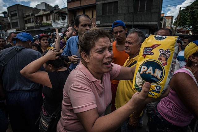 "A woman shakes a bag of corn flour, shouting ""Why is it so difficult for me to buy this?"" as hundreds of people wait in line to buy food at a grocery store in Catia, a barrio in western Caracas, Venezuela, on June 11, 2016. (Photo: Meridith Kohut / The New York Times)"