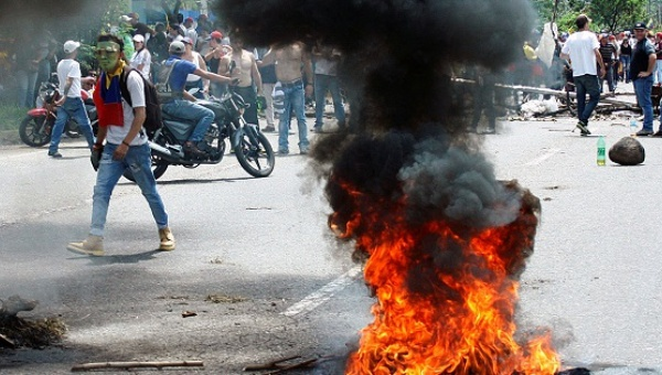 A demonstrator walks past a burning tire during an right-wing protest demanding the ouster of President Maduro in San Cristobal, Venezuela, Oct. 26, 2016. (Reuters)