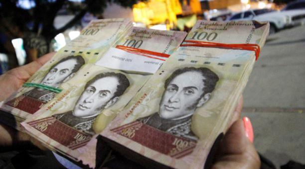 Women shows stacks of 100 Bolivar bills (AFP).