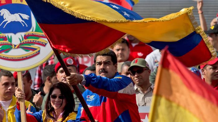 President Nicolás Maduro waves Venezuelan flag (Fernando Llano/AP).