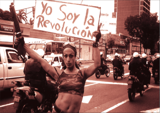 "Rummie Quintero holds a sign reading, ""I am the revolution."" (Archive)"