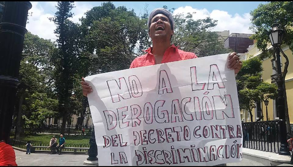 "Activist Leandro Villoria protests outside Carolina Cestari's office in downtown Caracas with poster that reads: ""No to the repeal of the anti-discrimination decree."" (Aporrea/Paola Martucci)"