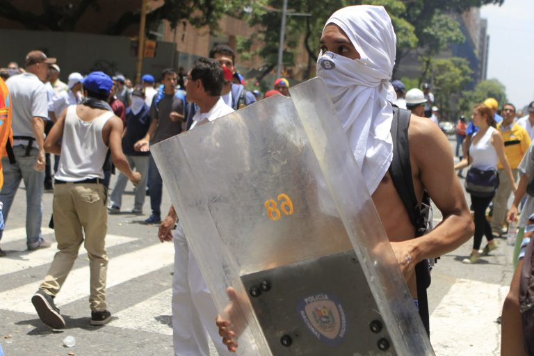 An anti-government demonstrator holds a police riot shield during a protest in Caracas on Tuesday. The Venezuelan opposition says its protesters are largely peaceful. (VTV)