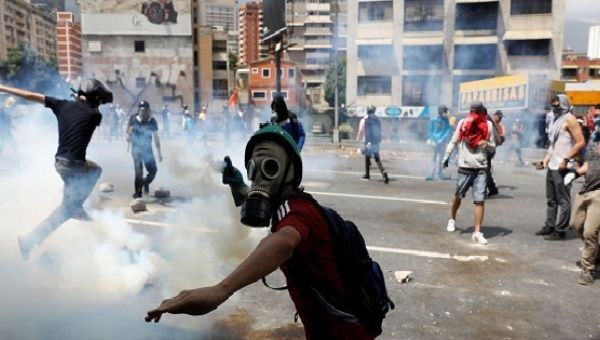 A demonstrator throws a tear gas canister back to policemen during an opposition rally in Caracas, Venezuela, April 6, 2017. (Reuters)