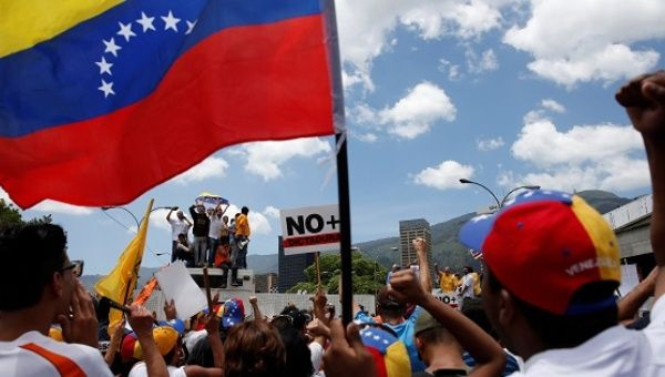 Opposition supporters holding a Venezuelan flag protest against Venezuela's President Nicolas Maduro's government during a rally in Caracas. (Reuters)