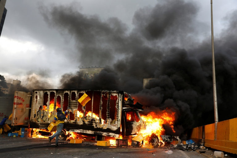 Venezuelan opposition protesters incinerate a truck as part of an anti-government barricade in Caracas on May 26. (Carlos García Rawlins/Reuters)