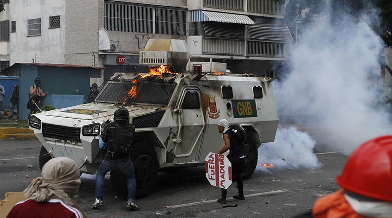 Protesters trying to force their way inside an APC in Caracas. The international media later carried reports complaining the vehicle ran over a protester. (AVN)