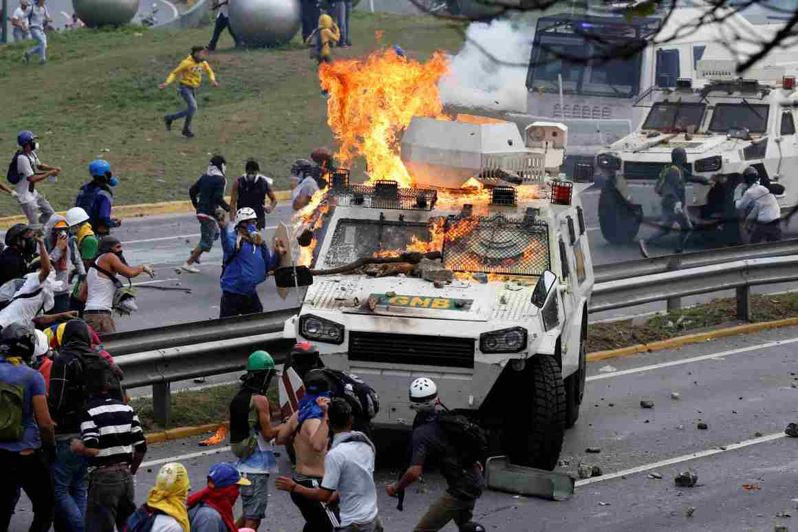 Venezuelan anti-government protesters attack a National Guard riot control vehicle on May 1st. (Reuters/Carlos Garcia Rawlins)