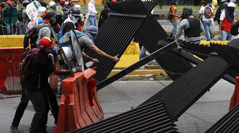 Protesters blocking a highway in Caracas, using fencing to create a barricade. (AVN)