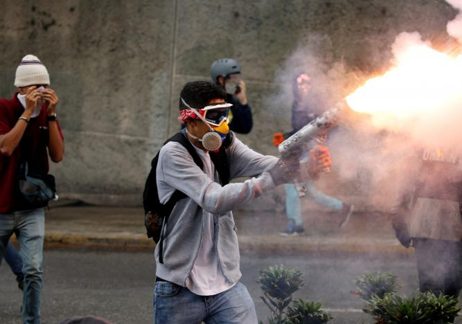 A protester fires at state security forces, using a home-made mortar (Reuters/Carlos Garcia Rawlins)