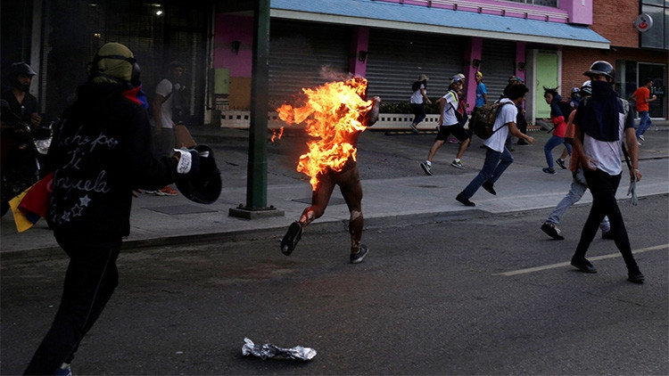 A man accused of being a supporter of President Nicolas Maduro was doused in gasoline and set on fire by opposition protesters Saturday. (Marco Bello/Reuters)