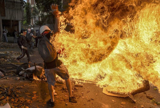 A protester is engulfed in flames after the National Guard motorbike he was trying to set on fire suddenly explodes. (Juan Barreto/AFP/Getty Images)