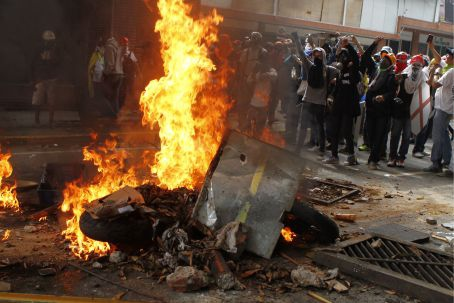 Venezuelan opposition protesters burn a National Bolivarian Police motorcycle at an anti-government barricade in the affluent eastern Caracas municipality of Chacao. (AVN)