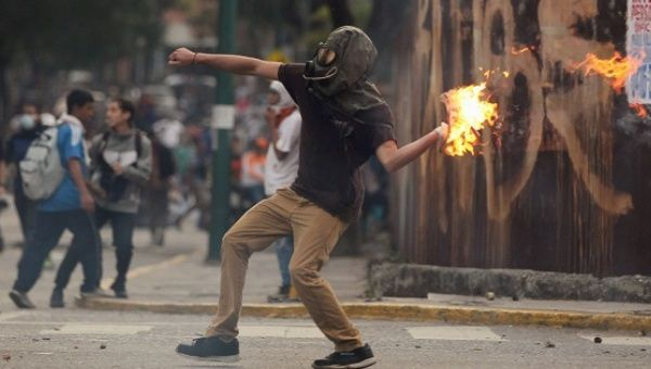 An opposition protester throws a molotov cocktail at police in Caracas. (Reuters)