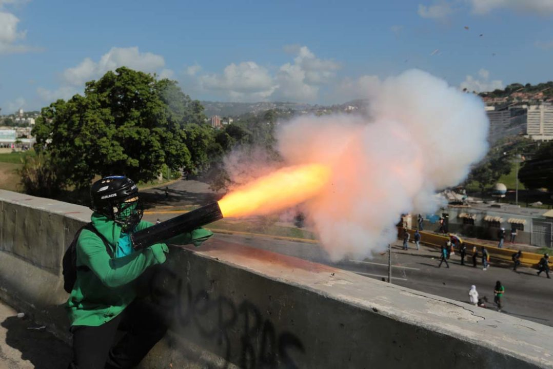 An opposition protester fires a home-made mortar in this photo taken on June 22 in Caracas. (Fernando Llano/AP)