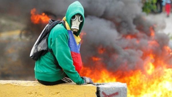 Demonstrator sits next to a fire barricade on a street during a rally against Venezuela's President Nicolas Maduro in Caracas, Venezuela April 24, 2017. (Reuters)