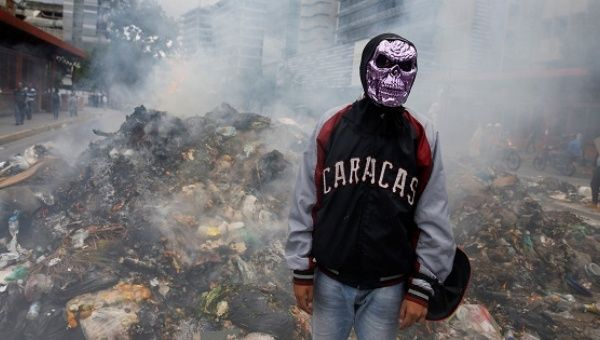 A Venezuelan opposition supporter in front of a barricade of smoldering rubble in Altamira, eastern Caracas. (Reuters)
