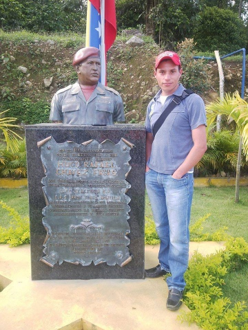 Commune youth leader Elvis Moreno standing next to a bust of Hugo Chavez