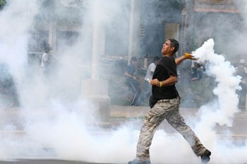 Opposition student throwing tear gas bomb at government supporters trapped inside the School of Social Work UCV (ABN)