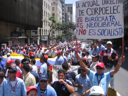 """An electrical worker's placard: """"The current managment of CORPOELEC is bureacratic, it is neoliberal, it is not socialist!"""""""