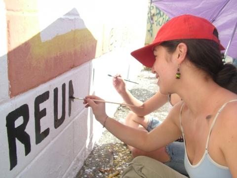 Lisbeida Rangel helping to paint a community noticeboard (Tamara Pearson)