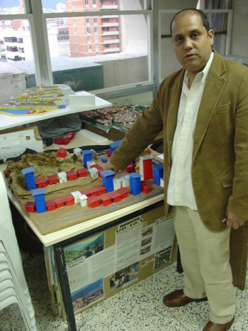 Ivan Martinez, the director of the national office for the regularization of urban land tenancy, shows some barrio models that CTU members built for the land title registration process. Credito: Alex Holland
