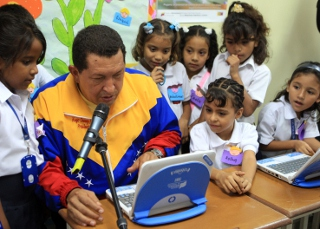 President Chavez examines a new children's laptop in a public school classroom (YVKE)