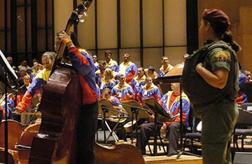 Members of Venezuela's Orchestra of the Penitentiary System practice while armed guards stand nearby (Archive).