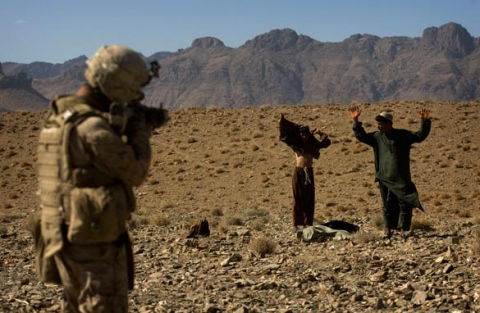 A U.S. Marine in Afghanistan points his weapon at two unidentified Afghan youth in Farah Province, southern Afghanistan (David Furst/AFP/Getty Images).