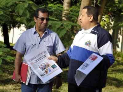 President Hugo Chavez (right) with newspapers to prove the date of the photo (Presidential Press)