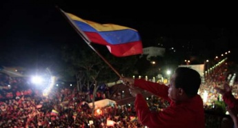 Hugo Chavez waving the Venezuelan flag to supporters from the People's Balcony of the presidential palace, Miraflores, on Sunday 7 October, after his victory was announced (AVN).