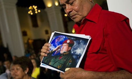 A supporter of the Venezuelan president holds a picture of him, as he attends a mass to pray for Chavez's health (Carlos Garcia Rawlins/Reuters)