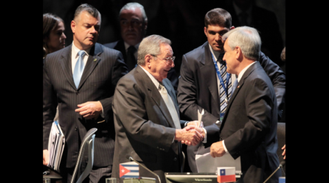 Raul Castro (middle), the Cuban president and new president pro tempore of CELAC shakes hands with the previous one, Sebastian Piñera of Chile.