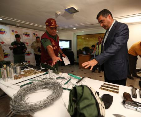Weapons displayed to state media by Interior Affairs Minister Rodriguez Torres (right) today. (AVN)
